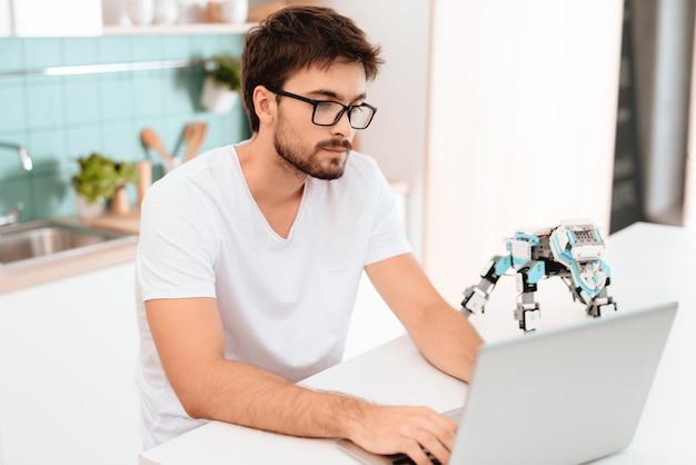 Robô pequeno fica na mesa. guy projetando robôs.