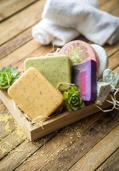 Robôs artesanais de sabonete de spa em uma caixa de madeira sobre um fundo de madeira, conceito de beleza e cuidados com o corpo