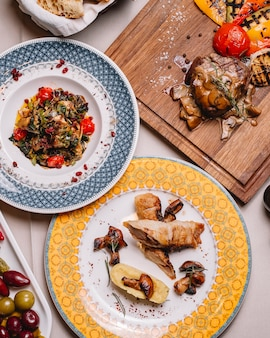 Rocambole de frango vista superior com purê de batatas cogumelos salada de legumes grelhada e carne vermelha com cogumelos e molho em cima da mesa