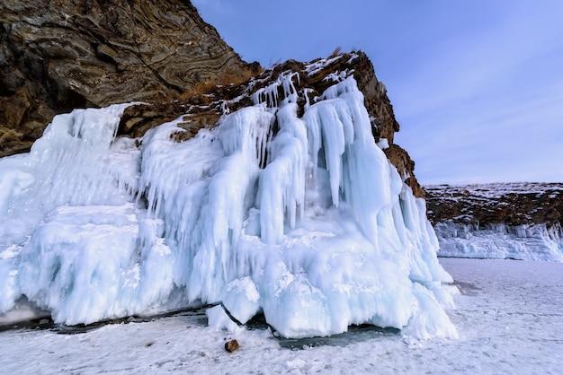 Rocha coberta com pingentes de gelo. lago baikal em tempo nublado.