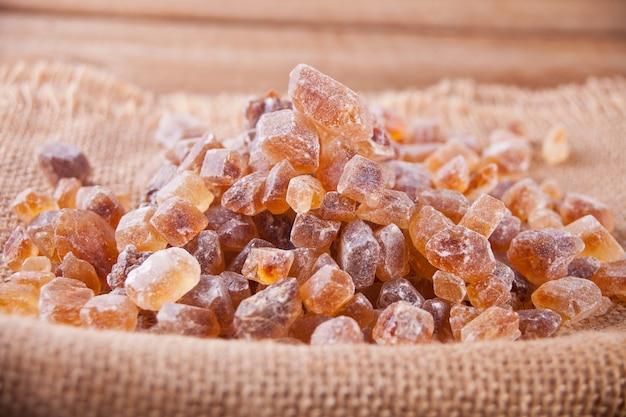 Rocha de açúcar mascavo orgânico cristalino em um guardanapo de juta