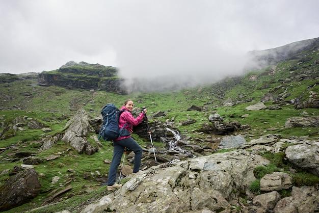 Rocha de escalada turista feminina com bengalas