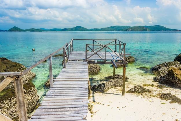 Rocha de ilha tropical e ponte de madeira na praia