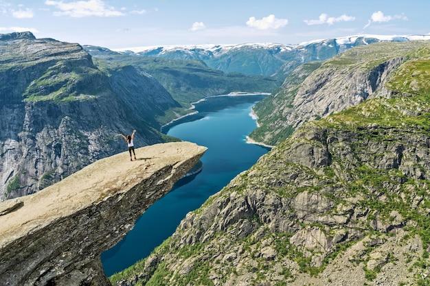Rocha trolltunga acima do lago de montanha ringedalsvatnet - famoso marco turístico norueguês de caminhadas com a garota de pé na rocha, noruega.