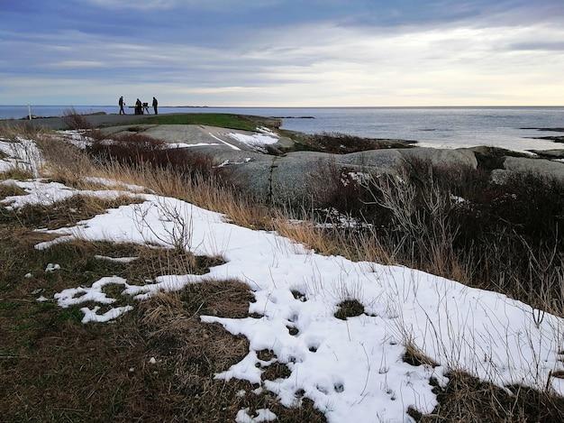 Rochas cobertas de galhos e neve cercadas pelo mar sob um céu nublado em rakke, na noruega