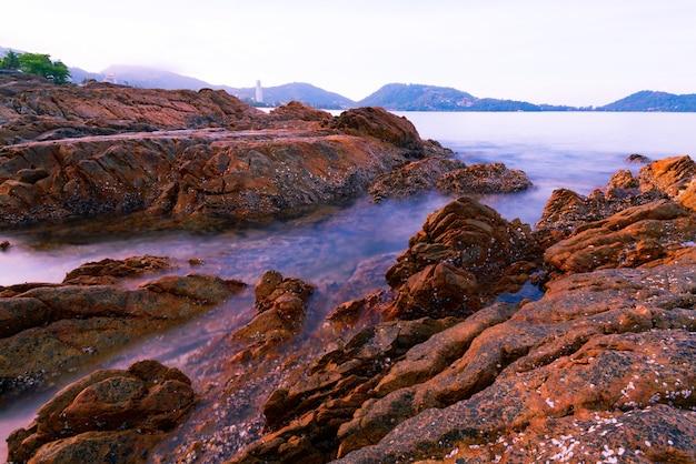 Rochas coloridas e ondas quebrando na praia grandes pedras coloridas.