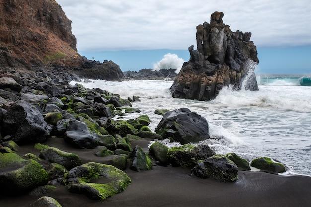 Rochas com musgo e mar agitado na praia