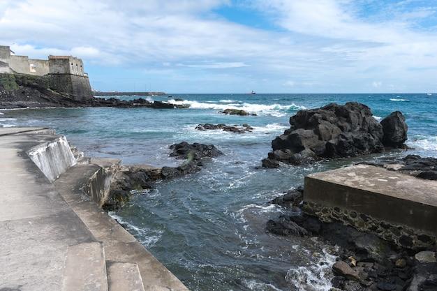 Rochas da costa em açores. ondas espirrando em rochas de basalto