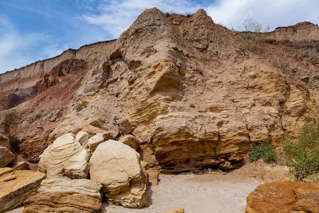 Rochas de areia amarela e pedras de várias formas na costa do mar negro. céu azul e água turquesa.