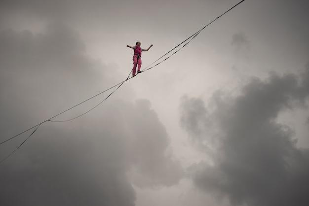 Rochas de um lago triangular, rússia - 2 de agosto de 2021: uma garota caminhante na corda caminha ao longo da linha alta contra o fundo de um céu dramático