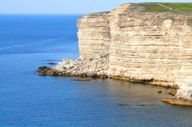 Rochas do mar negro no litoral, com águas azuis claras e céu azul