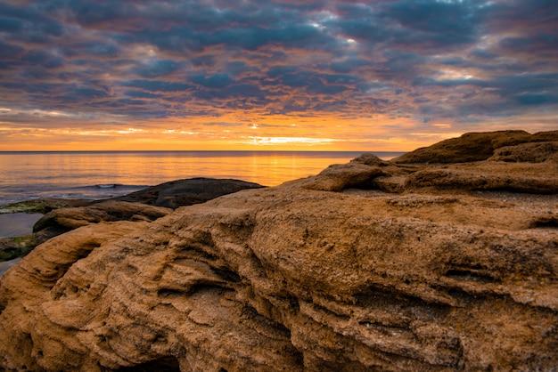 Rochas do sandy beach coloridas na laranja sob os raios do sol de aumentação.
