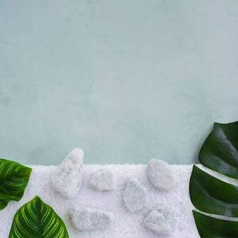 Rochas e folhas na toalha com espaço de cópia