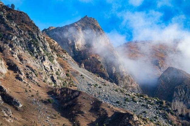 Rochas e nuvens nas montanhas do norte do cáucaso no outono em dia ensolarado