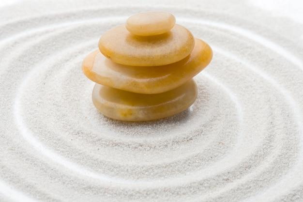 Rochas em equilíbrio com areia formando círculos fundo