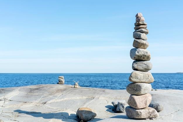 Rochas empilhadas que equilibram, empilhando com precisão. torre de pedra na costa. copie o espaço.