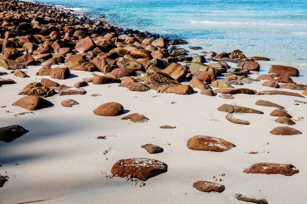 Rochas na areia com a luz solar.