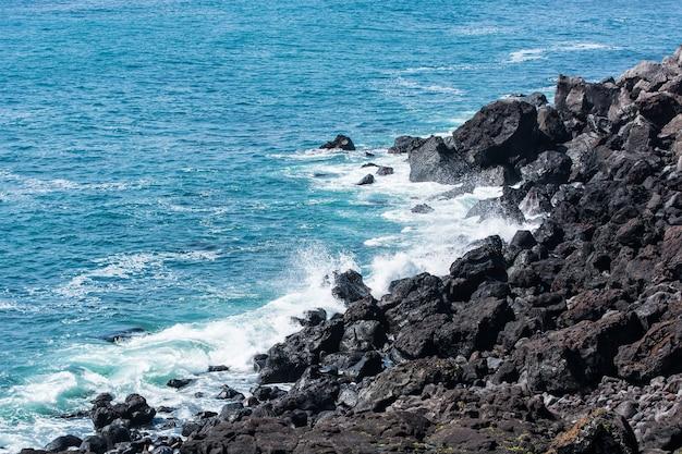 Rochas na praia com água do mar clara na ilha coreia do sul de seopjikoji jeju.