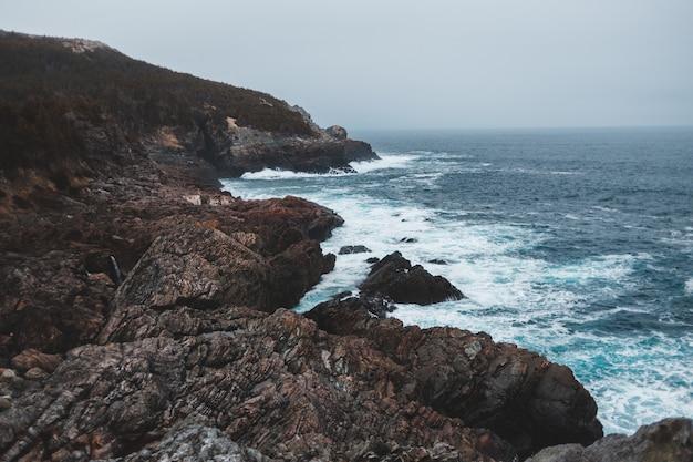 Rochas perto das ondas do mar em tempo nublado