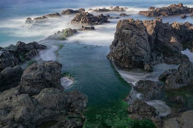 Rochas vulcânicas com musgo verde, litoral de puerto de la cruz, tenerife, ilhas canárias, espanha