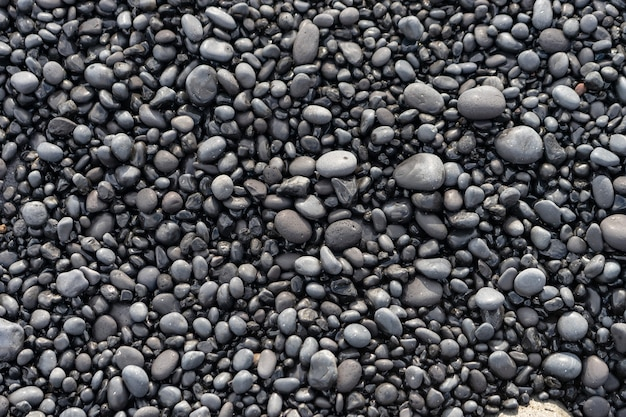 Rochas vulcânicas na areia preta da praia da islândia