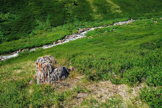 Rock na encosta da colina na angra de montanha diagonal de fundo no vale na luz solar.