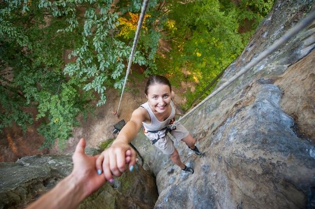 Rockclimber ajudando a alpinista feminina para chegar ao topo da montanha