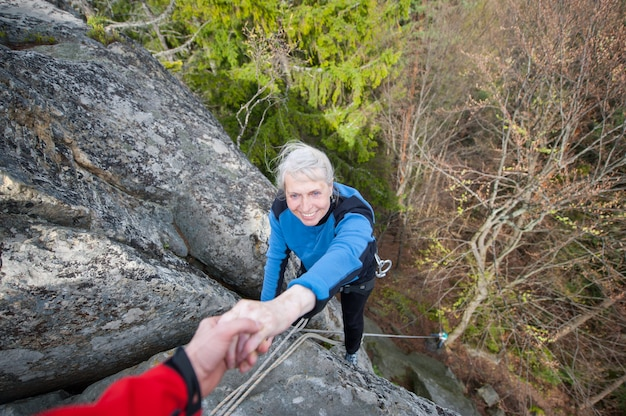 Rockclimber masculino está ajudando um alpinista para chegar a um pico de montanha