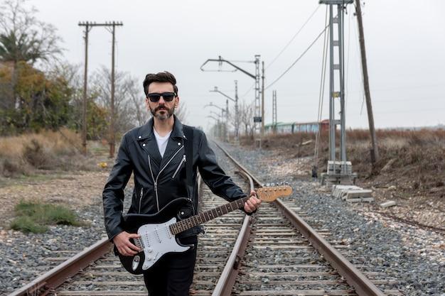 Rocker com óculos de sol andando com sua guitarra elétrica em trilhos de trem abandonados.