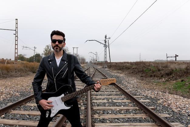 Rocker com óculos de sol tocando guitarra elétrica em trilhos de trem abandonados.
