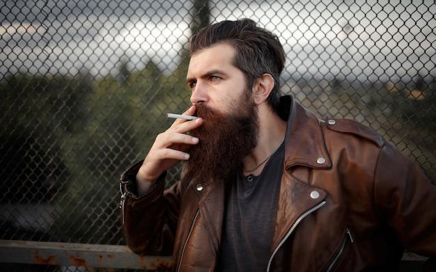 Rocker com uma longa barba, bigode e cabelos grisalhos em uma jaqueta de couro marrom fuma cigarros e olha para longe