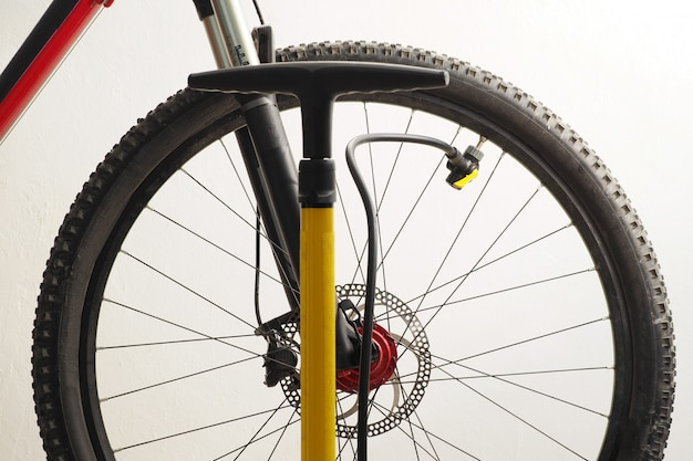 Roda de bicicleta de montanha e bomba de bicicleta amarela.