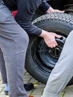 Roda de carro com pneu de borracha preta nas mãos de um homem troca sazonal de pneus