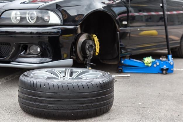 Roda de carro desmontada no primeiro plano.