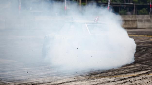 Roda de carro girando e criando cascatas de fumaça, drag racing em pista de corrida de velocidade,
