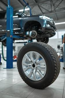 Roda de carro no chão em oficina mecânica