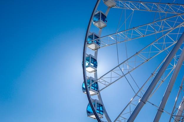 Roda de ferris branca com as cabines azuis clássicas de vidro contra o céu, helsínquia, finlandia.