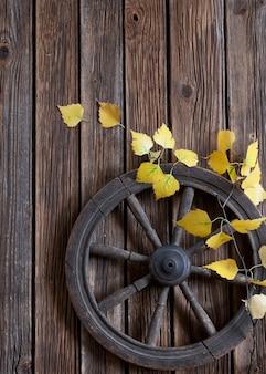 Roda de fiar e ramo de folhas amarelas de outono
