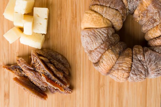 Roda de figos secos com um figo seco cortado em fatias ao lado de pedaços de queijo pecorino em cima da placa de madeira