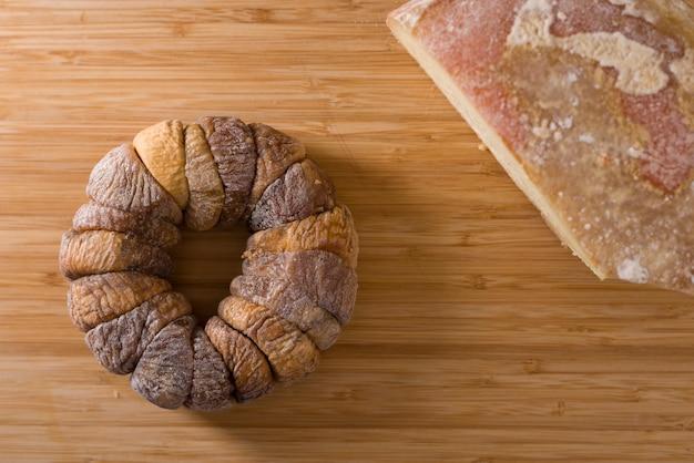 Roda de figos secos com um pecorino em cima da placa de madeira sobre uma toalha de mesa branca