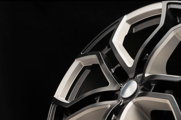 Roda de liga de alumínio. elenco premium, o design dos raios e o aro da roda, elementos brancos e pretos em close-up de fundo escuro