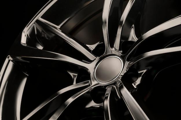 Roda de liga leve de brilho preto em um fundo escuro. elegante e caro. close-up de elementos de raio,