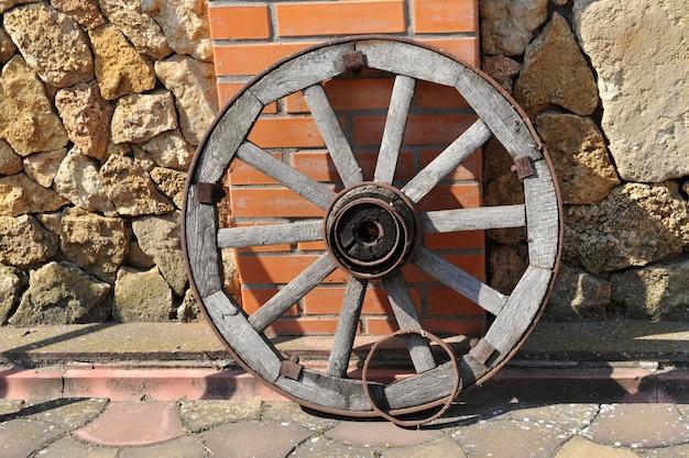 Roda de madeira antiga contra uma parede de tijolos.