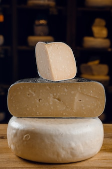 Roda de queijo de cabra e grandes pedaços dela. mix de queijos de leite de cabra.