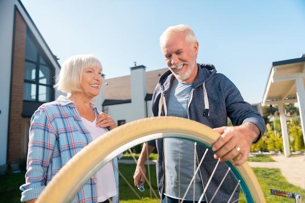 Roda de reparação. esposa e marido radiantes e alegres consertando a roda de uma bicicleta velha em frente à casa de verão