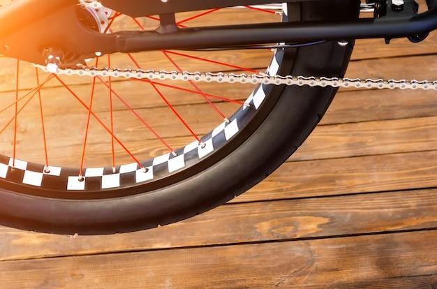Roda de uma bicicleta elegante com um aro preto e branco e um pneu de borracha preto sobre um fundo de madeira elegante.