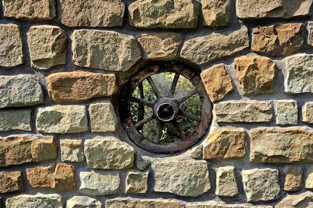 Roda decorativa vintage em parede de pedras