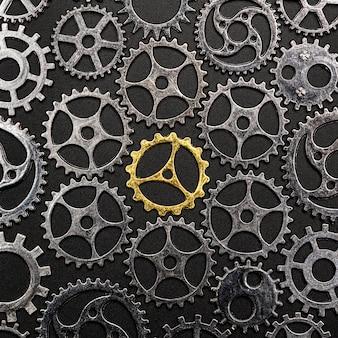 Roda denteada dourada cercada por rodas denteadas do metal.