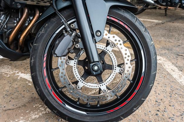 Roda dianteira próxima acima do sistema de freios em uma motocicleta moderna moderna com freios a disco.