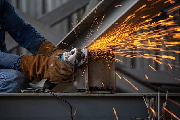 Roda elétrica de moagem em estrutura de aço e soldadores com múltiplas faíscas na fábrica.